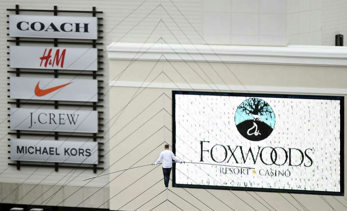 Famed aerialist Nik Wallenda walks a tightrope strung 75-80 feet off the ground for 711-feet between the Rainmaker parking garage and the new Tanger Outlets at Foxwoods, Friday, May 22, 2015 in Mashantucket, Conn. Wallenda's appearance was part of a string of festivities marking the opening of the mall. (Sean D. Elliot(/The Day via AP) MANDATORY CREDIT