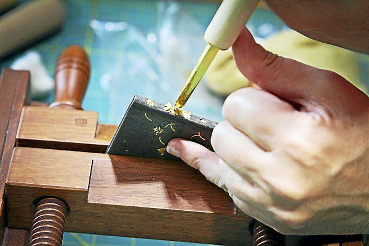 """American binder Gabrielle Fox tools with gold leaf for her mini-book """"Queen Mab."""""""