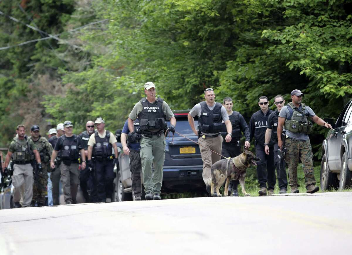 Law enforcement officers walk along a road as the search continues for two escaped prisoners from the Clinton Correctional Facility in Dannemora, on Monday, June 22, 2015, in Owls Head, N.Y. In the more than two weeks since inmates David Sweat and Richard Matt escaped, more than 800 law enforcement officers have gone door-to-door checking houses, wooded areas, campgrounds and summer homes. (AP Photo/Mike Groll)