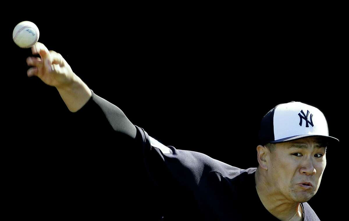 New York Yankees pitcher Masahiro Tanaka throws in the bullpen during a spring training baseball workout Monday.
