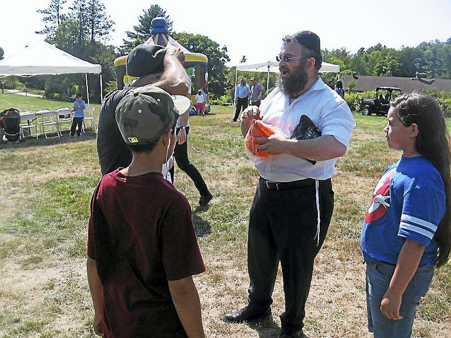 Rabbi Joseph Eisenbach, center, talks to festivalgoers. Photo: Journal Register Co.