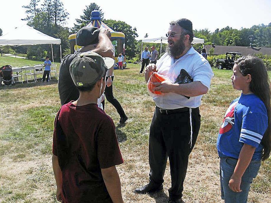 Rabbi Joseph Eisenbach, center, talks to festivalgoers. Photo: Journal Register Co.