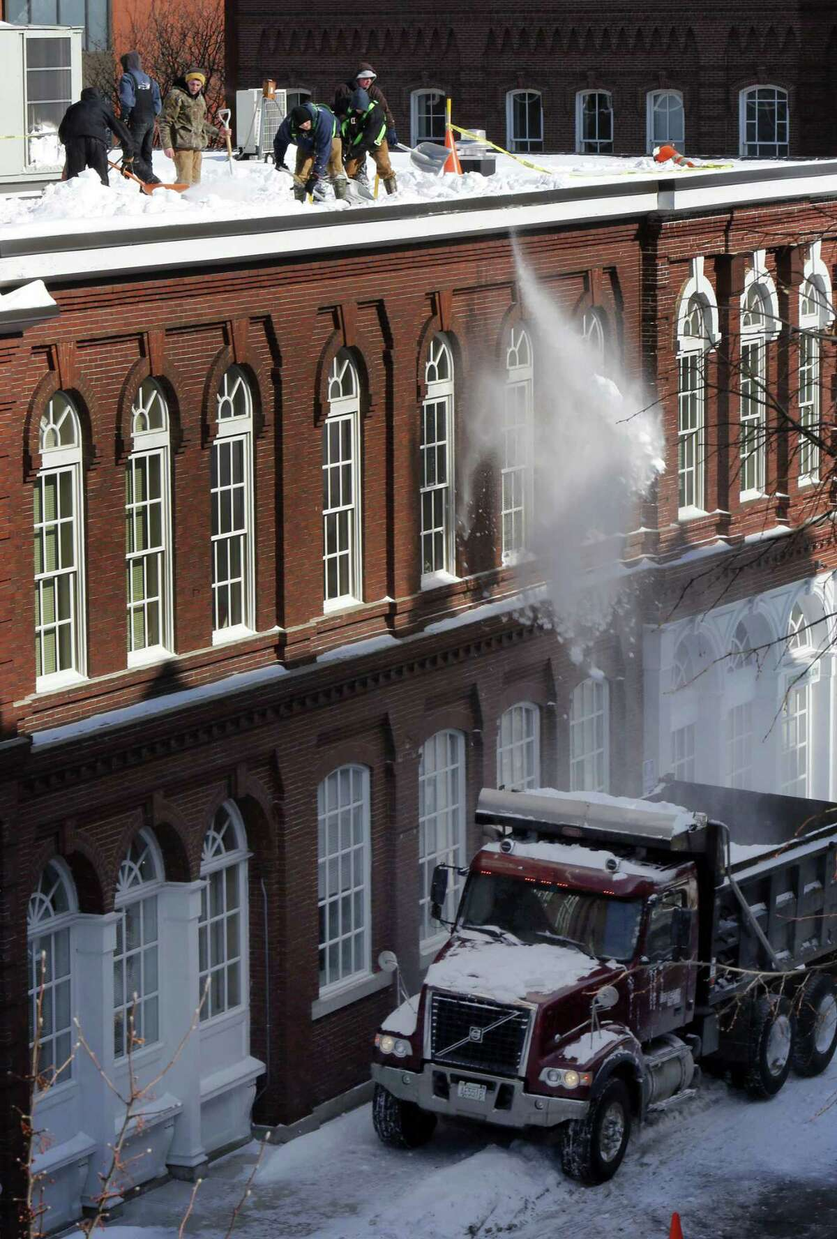 Crews continue to remove snow from roofs Friday, Feb. 20, 2015, in downtown Concord, N.H. The National Weather Service said as of Friday, it's been the coldest February on record for Concord, but that could change with a bit of a warm-up expected on Sunday. (AP Photo/Jim Cole)
