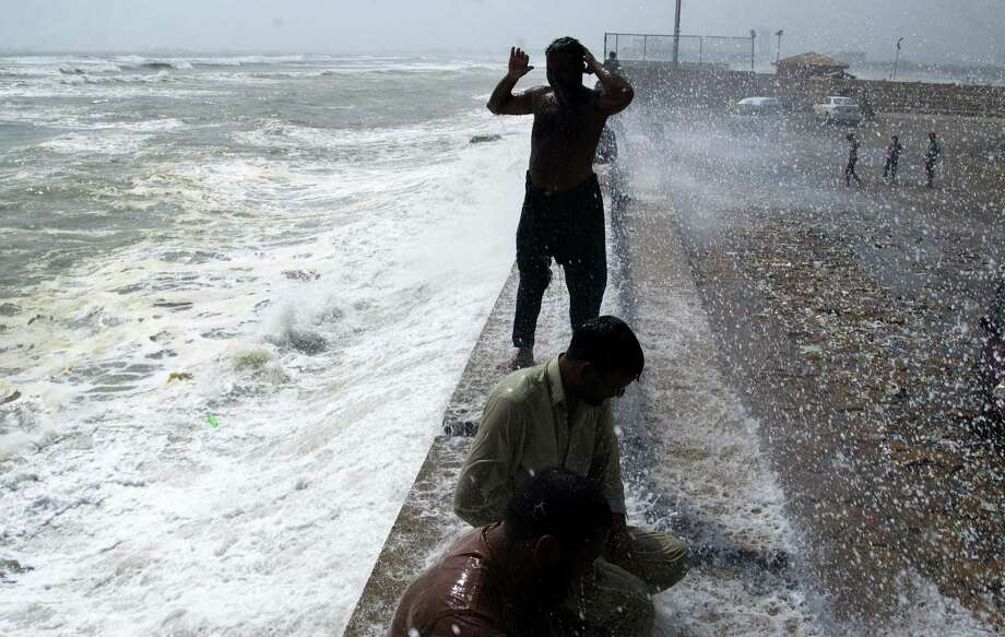People cool themselves off at Karachi's shore in Pakistan, Tuesday, June 23, 2015. A scorching heat wave across southern Pakistan's city of Karachi has killed more than 400 people, authorities said Tuesday, as morgues overflowed with the dead and overwhelmed hospitals struggled to aid those clinging to life. (AP Photo/Shakil Adil) Photo: AP / AP
