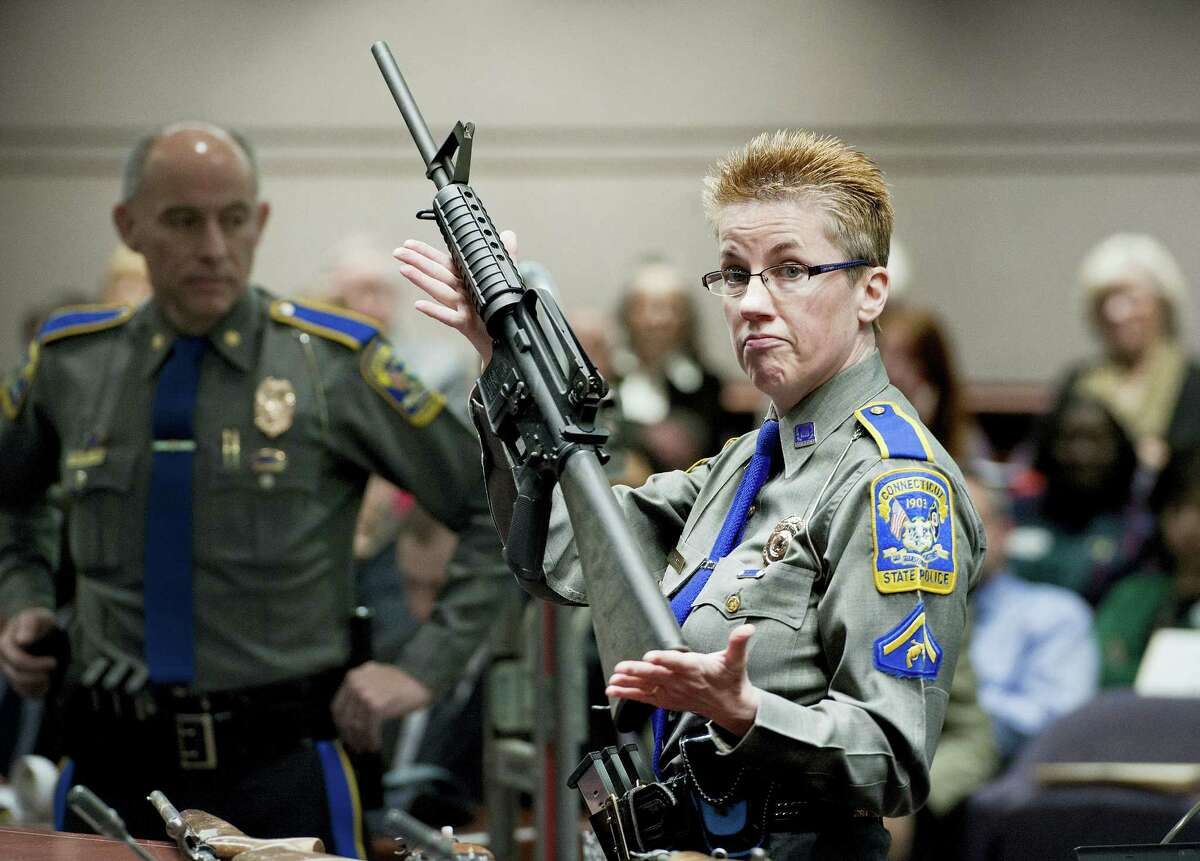 In this Jan. 28, 2013 photo, firearms training unit Detective Barbara J. Mattson, of the Connecticut State Police, holds up a Bushmaster AR-15 rifle, the same make and model of gun used by Adam Lanza in the Sandy Hook School shooting, during a hearing of a legislative subcommittee, at the Legislative Office Building in Hartford, Conn. Lawyers for the company that made the rifle Lanza used at Sandy Hook Elementary School in 2012 are expected to ask a Connecticut judge on Monday, Feb. 22, 2016 to dismiss a wrongful death lawsuit filed by families of some of the massacre victims.