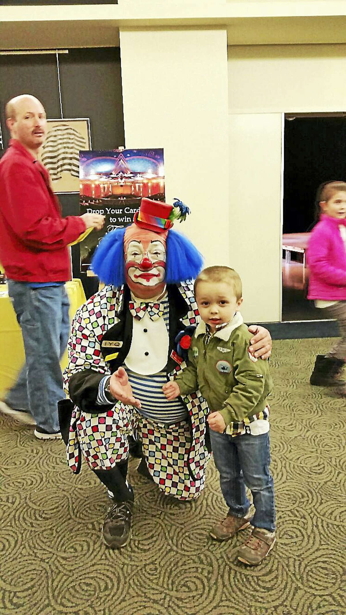 Lefty the Clown poses with Austin Brooks, 3, of New Hartford at the KidsPlay Children's Museum's second annual Family Fun Fair at the Warner Theatre.