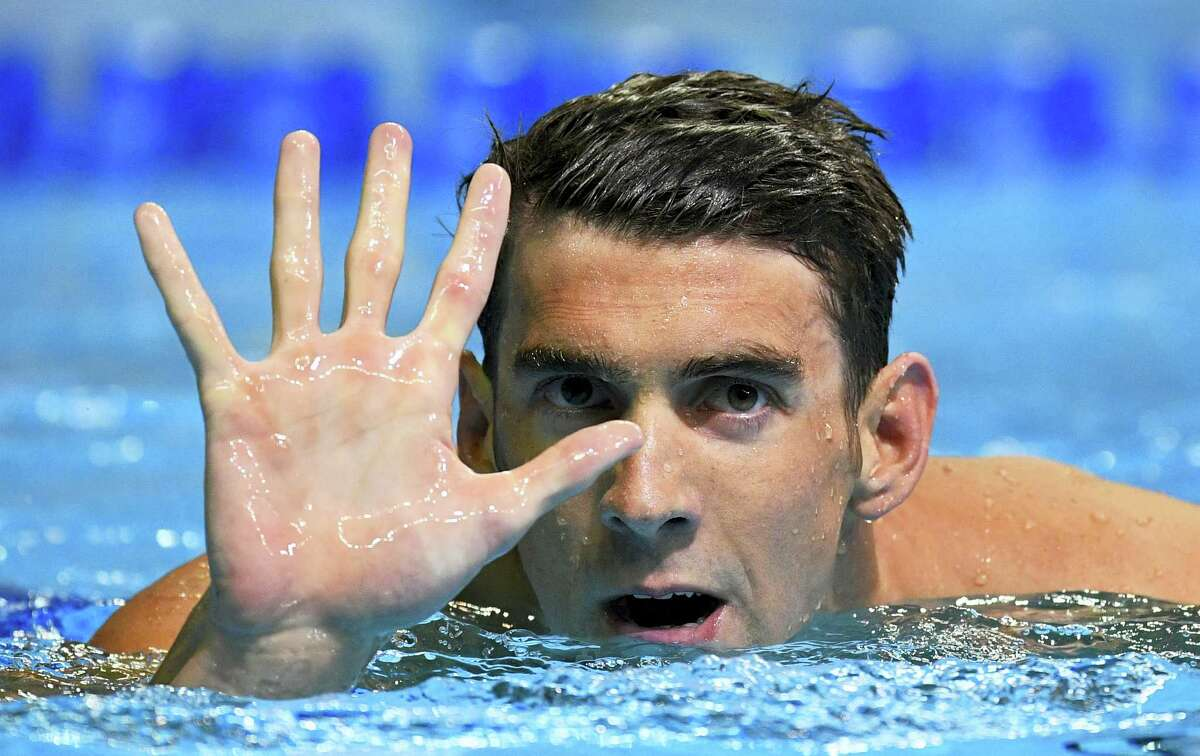 Michael Phelps puts up five fingers gestures after winning the men's 200-meter butterfly at the U.S. Olympic swimming trials Wednesday in Omaha, Neb. This will be Phelps' fifth trip to the Summer Olympics, which will take place in Rio in August.