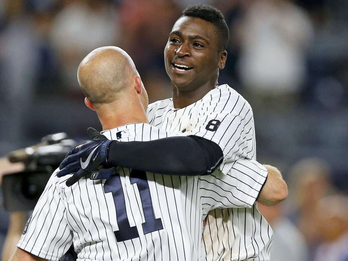 New York Yankees Brett Gardner (11) celebrates with the Didi Gregorius after Gregorius hit a ninth-inning, walk-off, two-run, homer to lift the Yankees to a 9-7 victory over the Texas Rangers in a baseball game in New York Wednesday.