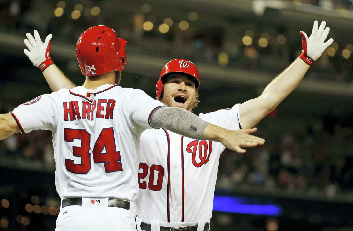 Washington Nationals' Bryce Harper (34) celebrates with Daniel Murphy (20) after Murphy's two-run home run during the eighth inning against the New York Mets at Nationals Park, Wednesday. The Nationals won 4-2.