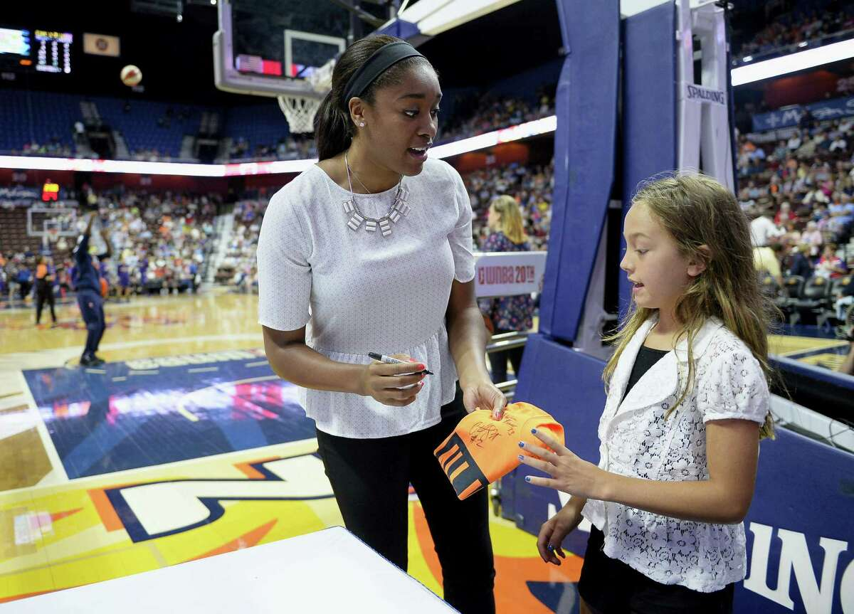 The Connecticut Sun's Morgan Tuck, left, gives an autograph to Kendall Kubachka as her team warms up before Friday's game against Phoenix in Uncasville. Tuck will miss the rest of the season because of a left knee injury.
