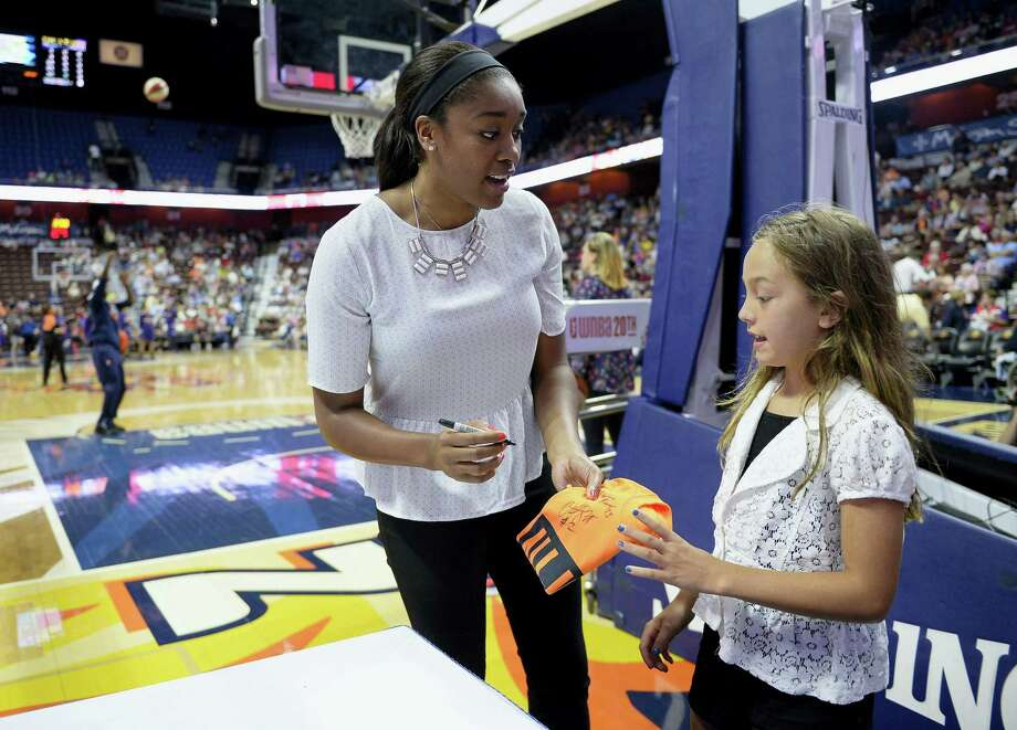 The Connecticut Sun's Morgan Tuck, left, gives an autograph to Kendall Kubachka as her team warms up before Friday's game against Phoenix in Uncasville. Tuck will miss the rest of the season because of a left knee injury. Photo: Jessica Hill — The Associated Press  / AP2016