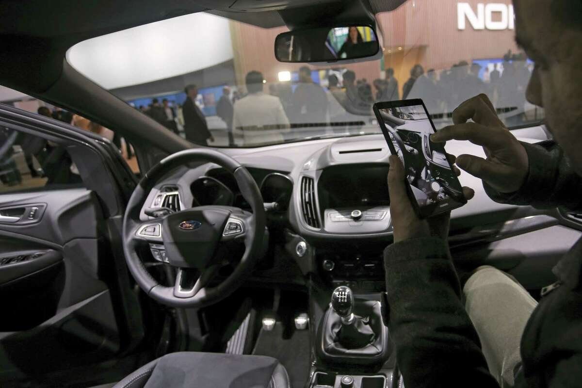 A man takes photographs with a phone inside the new Ford Kuga SUV car, which features its latest connectivity and driver-assisted technology, during the Mobile World Congress Wireless show, the world's largest mobile phone trade show, in Barcelona, Spain on Feb. 22, 2016.