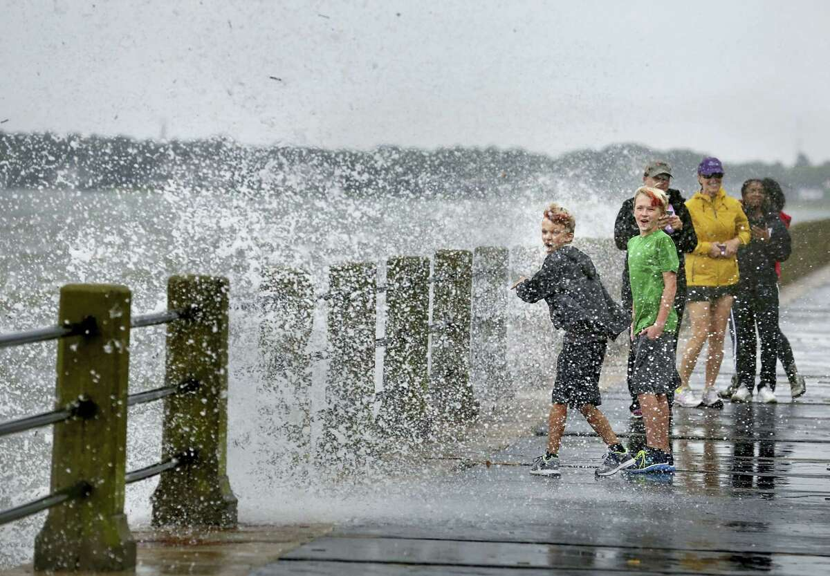 Brothers Trey Bowers,10 and Tyler Bowers,12, are splached with salt water from a crashing wave from Tropical Storm Hermine, Friday, Sept. 2, 2016, in Charleston, S.C.