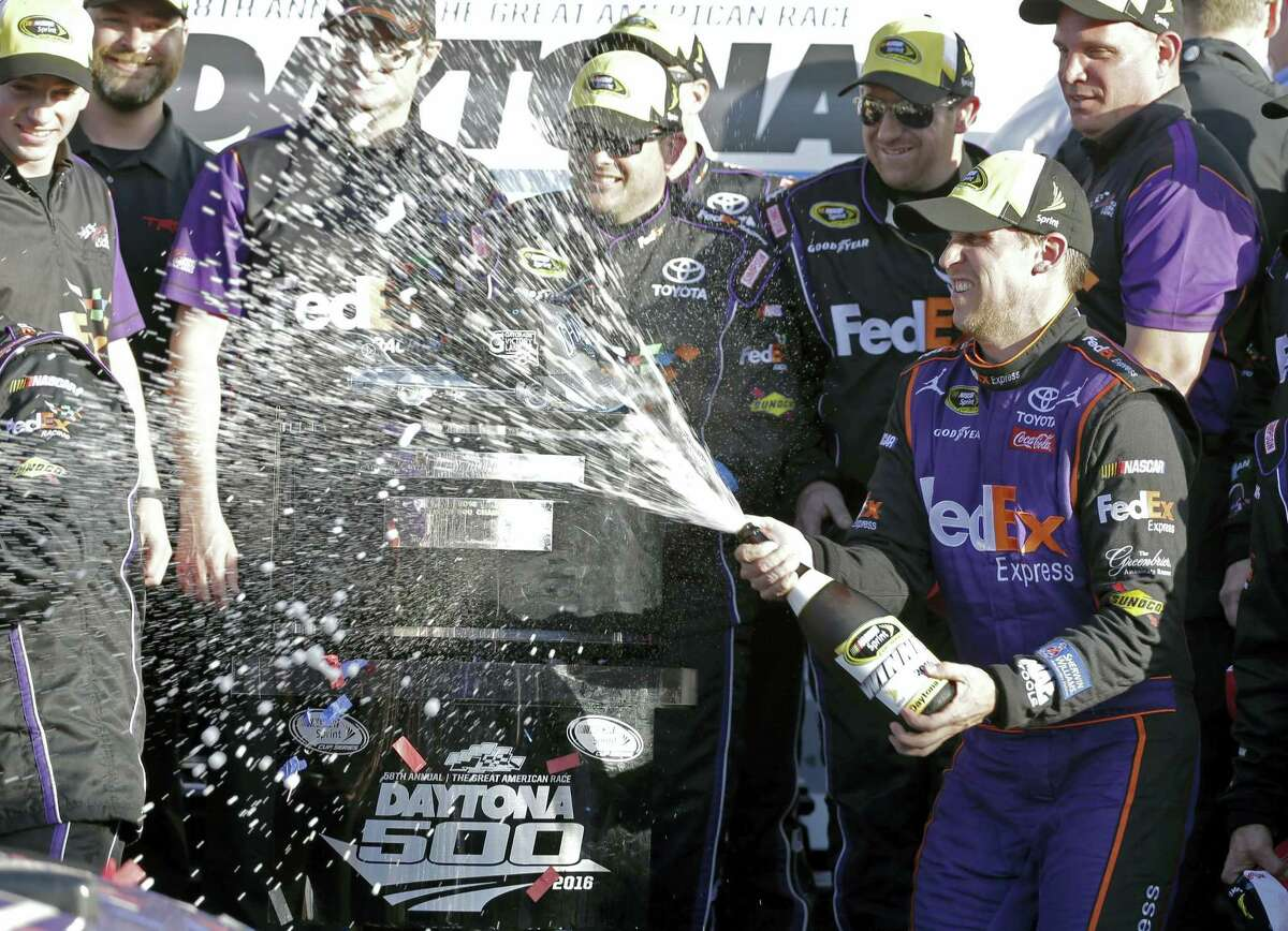 Denny Hamlin celebrates with his crew in Victory Lane after winning the NASCAR Daytona 500 Sprint Cup Series auto race at Daytona International Speedway in Daytona Beach, Fla., Sunday, Feb. 21, 2016. (AP Photo/Terry Renna)