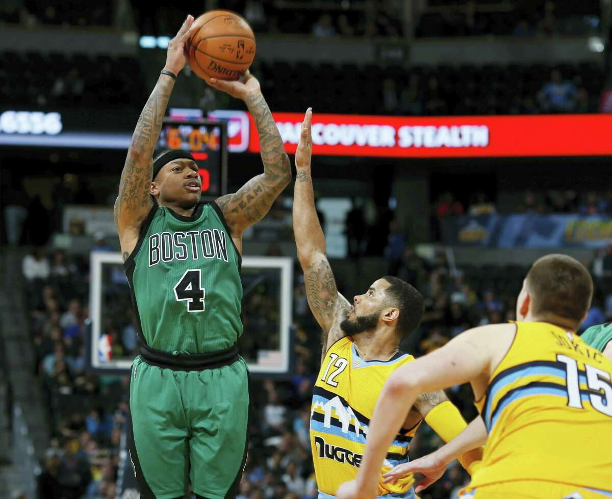 Boston Celtics guard Isaiah Thomas, left, goes up for three-point basket over Denver Nuggets guard D.J. Augustin, center, and center Nikola Jokic, of Serbia, in the second half of an NBA basketball game Sunday, Feb. 21, 2016, in Denver. Boston won 121-101. (AP Photo/David Zalubowski)