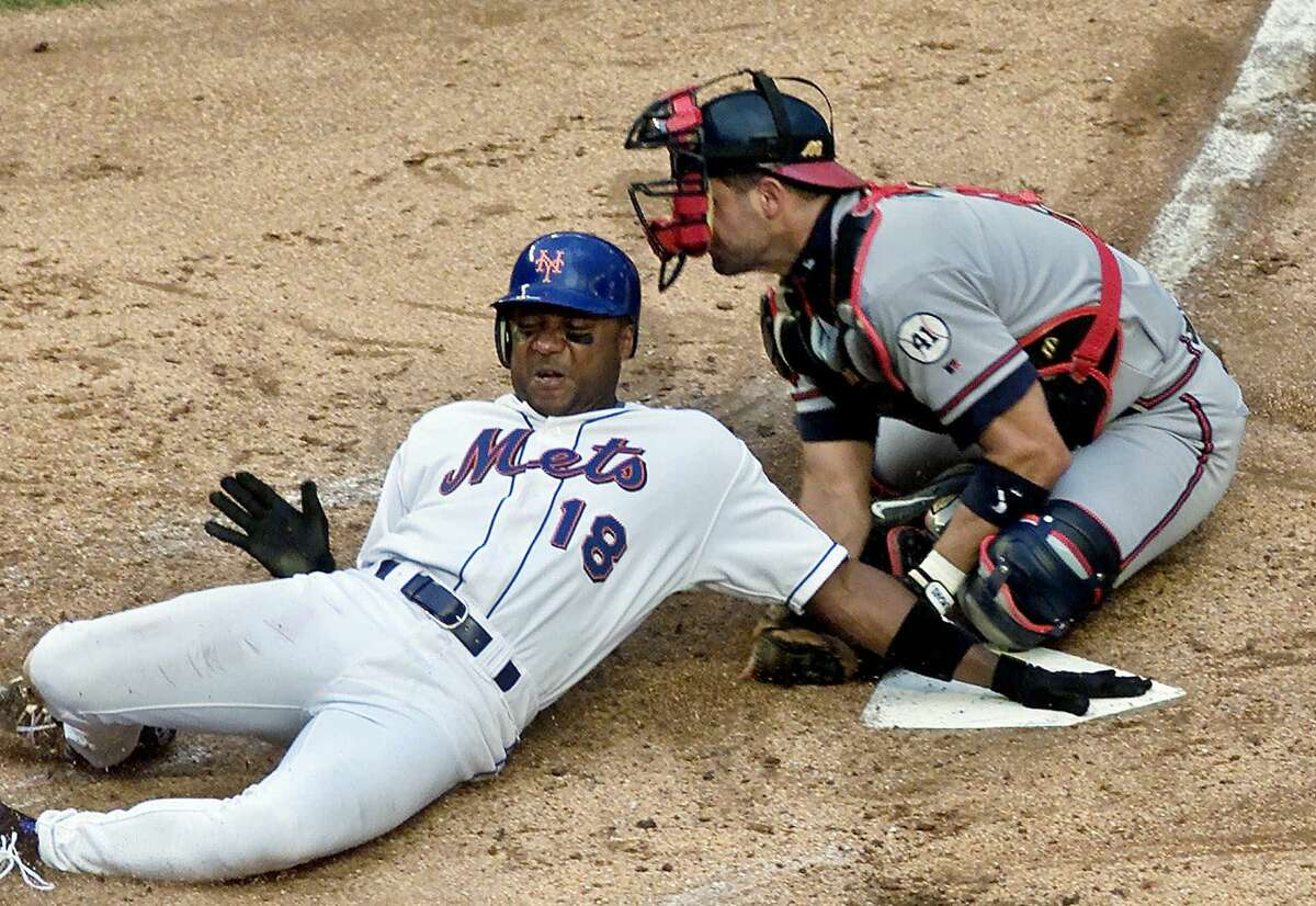 In this June 23, 2001 file photo, Mets outfielder Darryl Hamilton is tagged out at home by Atlanta Braves catcher Javy Lopez at Shea Stadium in New York. Authorities say Hamilton was killed Sunday in a murder-suicide in the Houston suburb of Pearland, Texas. Pearland police say an initial investigation has determined Hamilton had been shot several times and that a woman in the home died of a self-inflicted gunshot wound. The woman was identified as Monica Jordan.