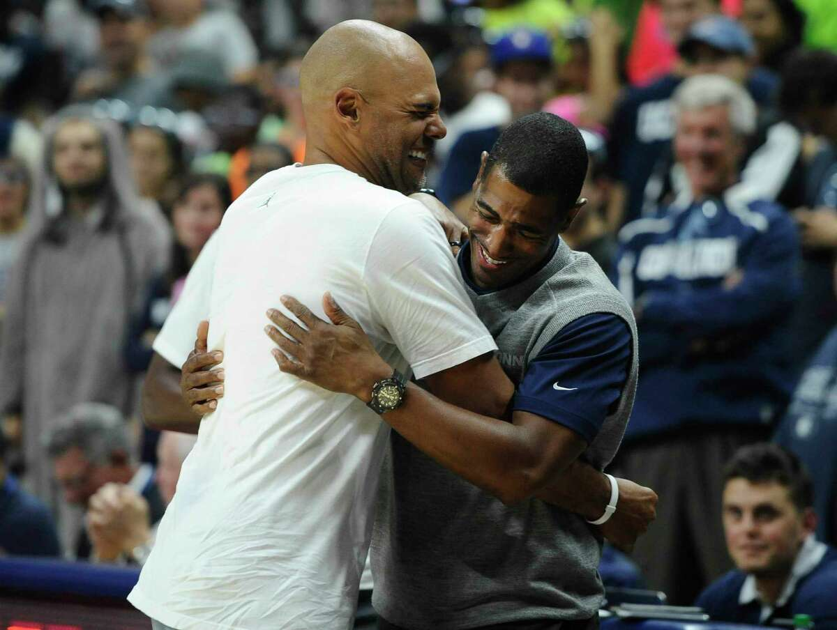 Former UConn star Donny Marshall, left, is embraced by head coach Kevin Ollie after Marshall won a 3-point shootout against Ray Allen at First Night on Friday in Storrs.