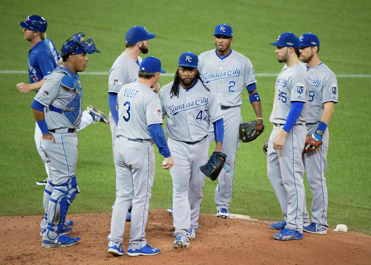 Kansas City Royals starting pitcher Johnny Cueto, center, walks off the mound after handing the ball to manager Ned Yost (3) during the third inning of Game 3 of the ALCS on Monday in Toronto.