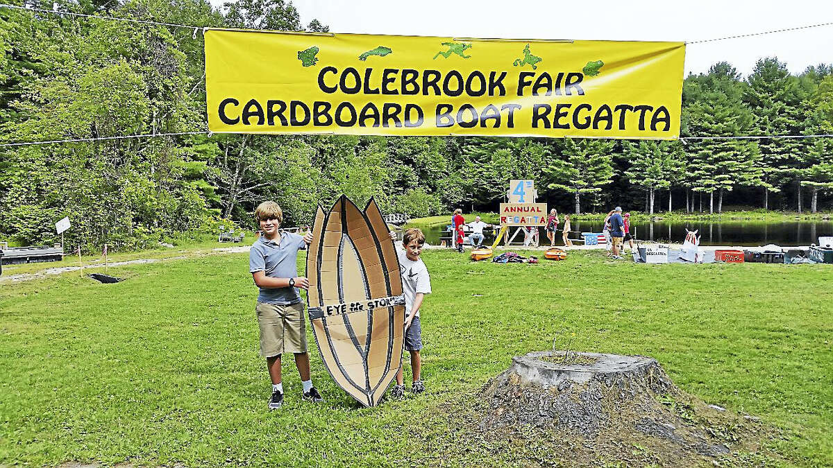 """Alec Vagliano, 11, and Nicolas Nino, 10, prepared to enter Vagliano's cardboard boat """"Eye of the Storm"""" into the Cardboard Boat Regatta at the 72nd annual Colebrook Fair at the intersection of Routes 183 and 182A on Saturday afternoon. The event, attended by about 1,000 visitors, featured 40 food and craft vendors; a magic act; a frog-jumping contest; live music; and firefighting drills for families."""