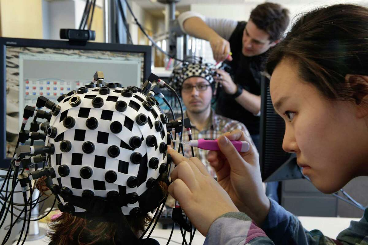 Undergraduate student Jenny Park, right, attaches laser probes to Shaw Bronner, as Adam Noah does the same to Shaul Yahil, at the Yale Brain Function Lab during a demonstration of brain mapping technology in New Haven this spring. At one end of each of the 64 fiber optic cables in each headpiece, weak laser beams saw about an inch into their brains to detect blood flow.