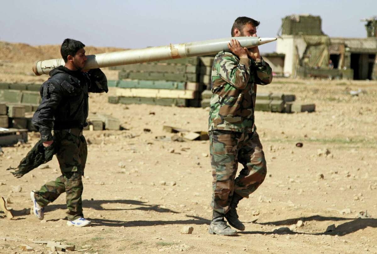 In this photo taken on Feb. 17, 2016, soldiers from the Syrian army carry a rocket to fire at Islamic State group positions in the province of Raqqa, Syria. In recent weeks, Syrian government forces captured dozens of villages and towns across the country.