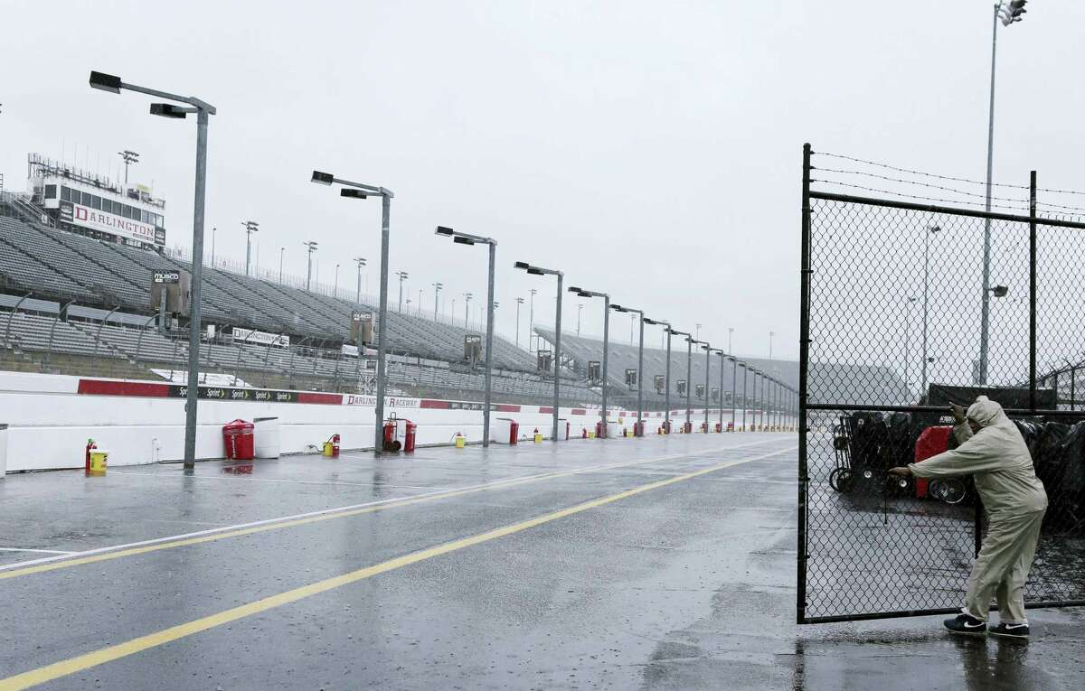 A security guard closes a gate in the garage area in the rain at Darlington Raceway on Friday.