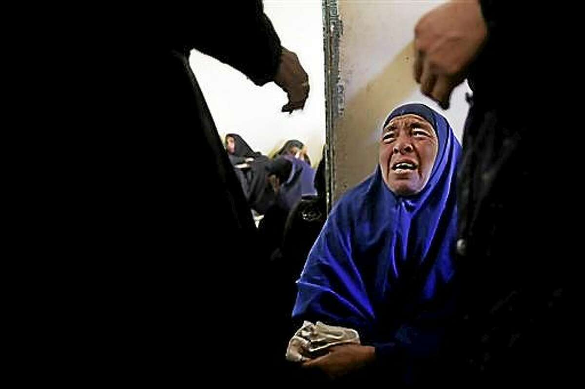 AP10ThingsToSee - A woman mourns for the Egyptian Coptic Christians who were captured in Libya and killed by militants affiliated with the Islamic State group, inside the Virgin Mary Church in the village of el-Aour, near Minya, Egypt, 220 kilometers (135 miles) south of Cairo, on Monday, Feb. 16, 2015. Egyptian warplanes struck Islamic State targets in Libya on Monday in swift retribution for the extremists' beheading of a group of Egyptian Christian hostages on a beach, shown in a grisly online video released hours earlier. (AP Photo/Hassan Ammar)
