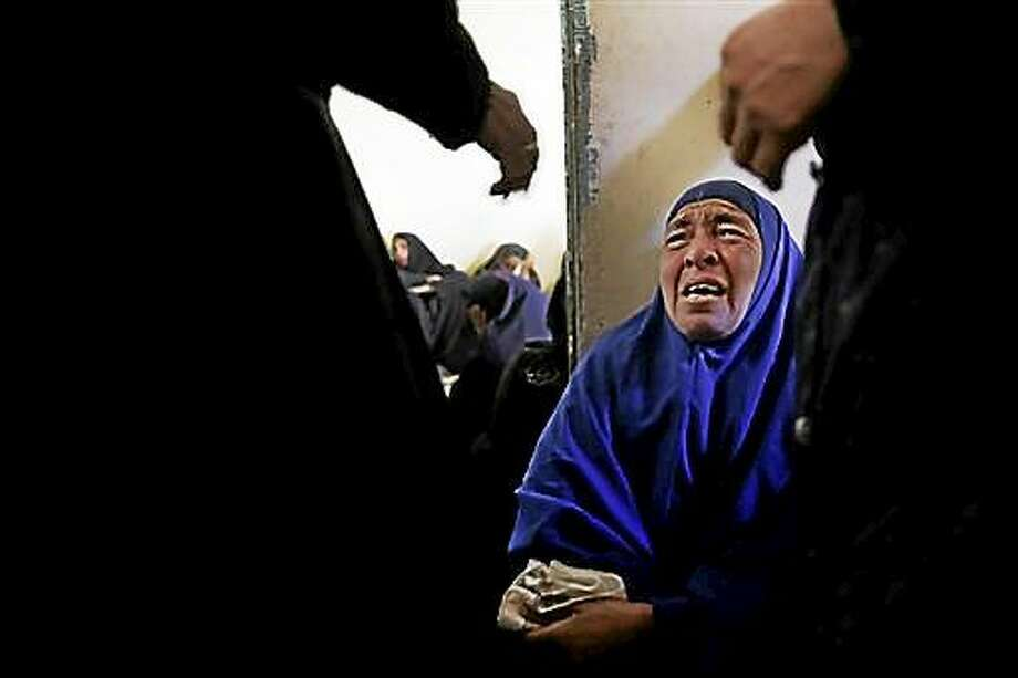 AP10ThingsToSee - A woman mourns for the Egyptian Coptic Christians who were captured in Libya and killed by militants affiliated with the Islamic State group, inside the Virgin Mary Church in the village of el-Aour, near Minya, Egypt, 220 kilometers (135 miles) south of Cairo, on Monday, Feb. 16, 2015. Egyptian warplanes struck Islamic State targets in Libya on Monday in swift retribution for the extremists' beheading of a group of Egyptian Christian hostages on a beach, shown in a grisly online video released hours earlier. (AP Photo/Hassan Ammar) Photo: AP / AP