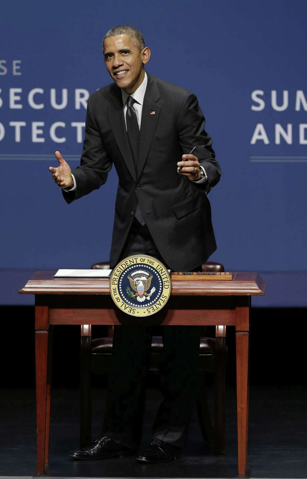 President Barack Obama smiles while signing an executive order after speaking at the White House Summit on Cybersecurity and Consumer Protection in Stanford, Calif., Friday, Feb. 13, 2015. (AP Photo/Jeff Chiu)