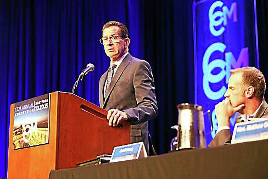 Gov. Dannel P. Malloy addresses local elected officials as CCM Executive Director Joe DeLong listens. Photo: Christine Stuart — CT News Junkie