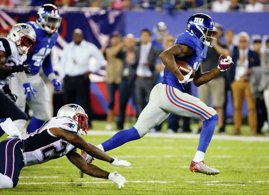 Giants wide receiver Tavarres King, right, runs away from the Patriots' Cyrus Jones for a touchdown during the second half on Thursday. Photo: Kathy Willens — The Associated Press  / Copyright 2016 The Associated Press. All rights reserved.