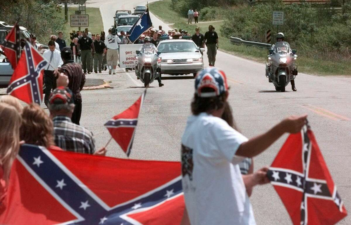 In this April 3, 2000 file photo, marchers make their way along Old State Road and are met by Confederate flag supporters near Moncks Corner, S.C.