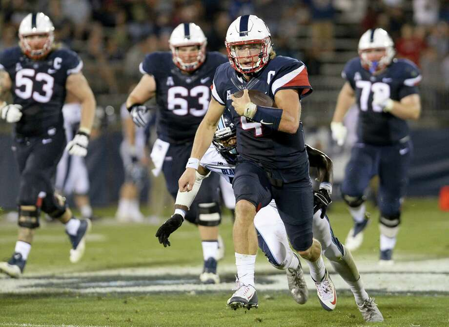 UConn quarterback Bryant Shirreffs pulls away from Maine's Benjamin Davis during the second half on Thursday. Photo: Jessica Hill — The Associated Press  / AP2016