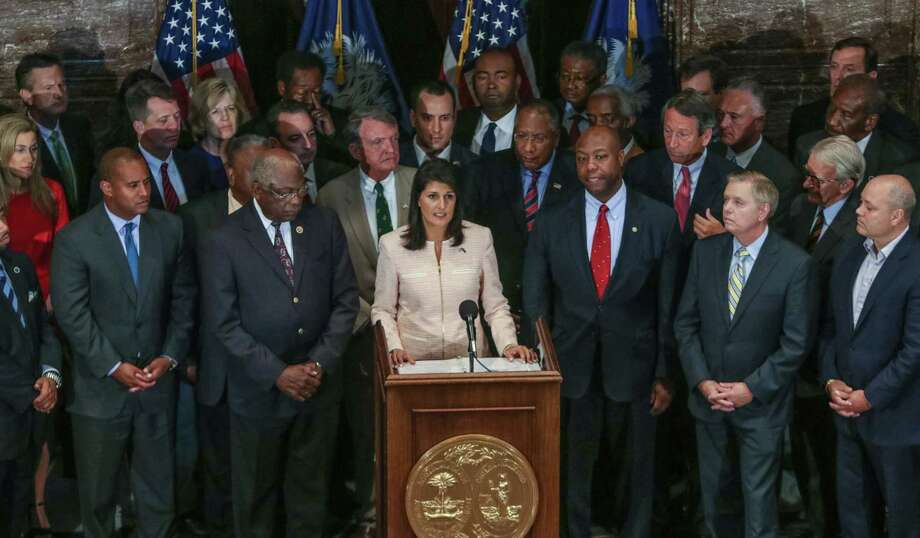 TIM DOMINICK/THE STATE VIA AP South Carolina Gov. Nikki Haley, center, calls for legislators to remove the Confederate flag from the Statehouse grounds during a news conference in the South Carolina State House in Columbia, S.C., Monday. Those surrounding her as she spoke included state legislators of both parties. Photo: AP / The State