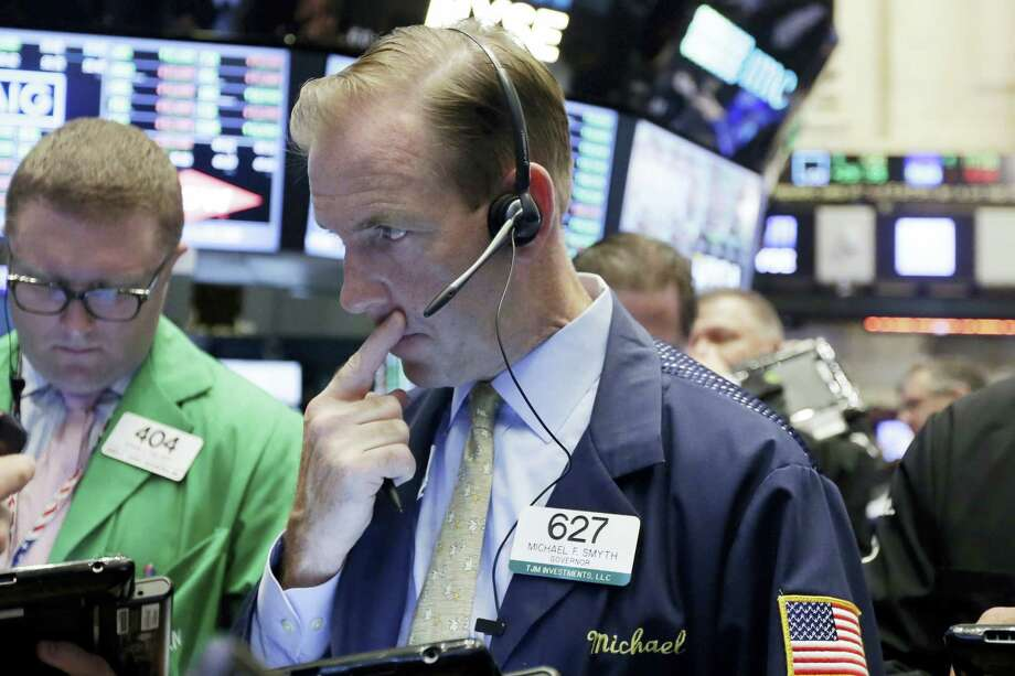 Trader Michael Smyth, center, works on the floor of the New York Stock Exchange Wednesday. Photo: Richard Drew — The Associated Press  / AP