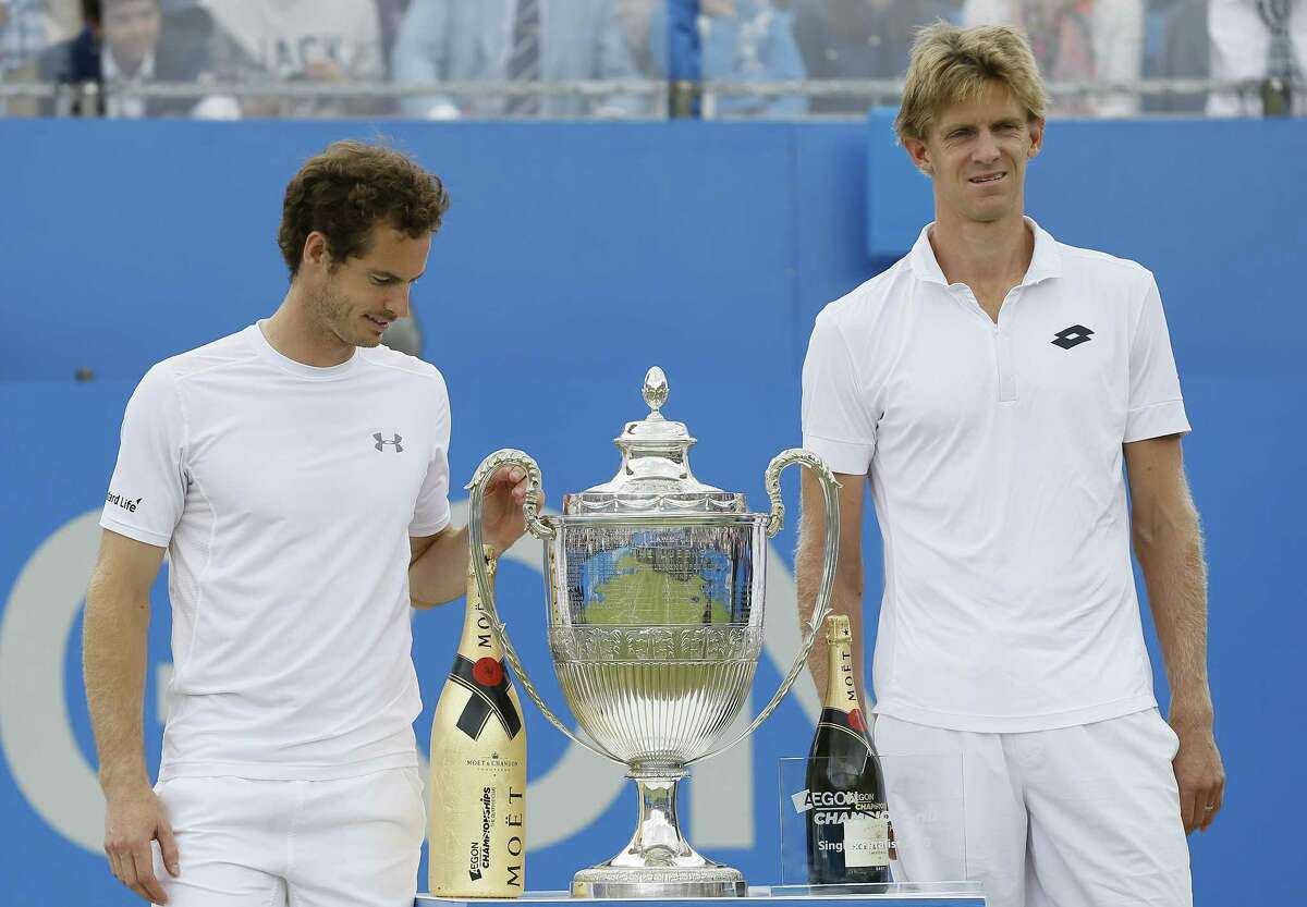 Winner Andy Murray of Britain, left, and runner up Kevin Anderson of South Africa, right, pose for a photograph with their trophies after their final tennis match at the tennis Championships at Queens Club in London on Sunday, June 21, 2015.
