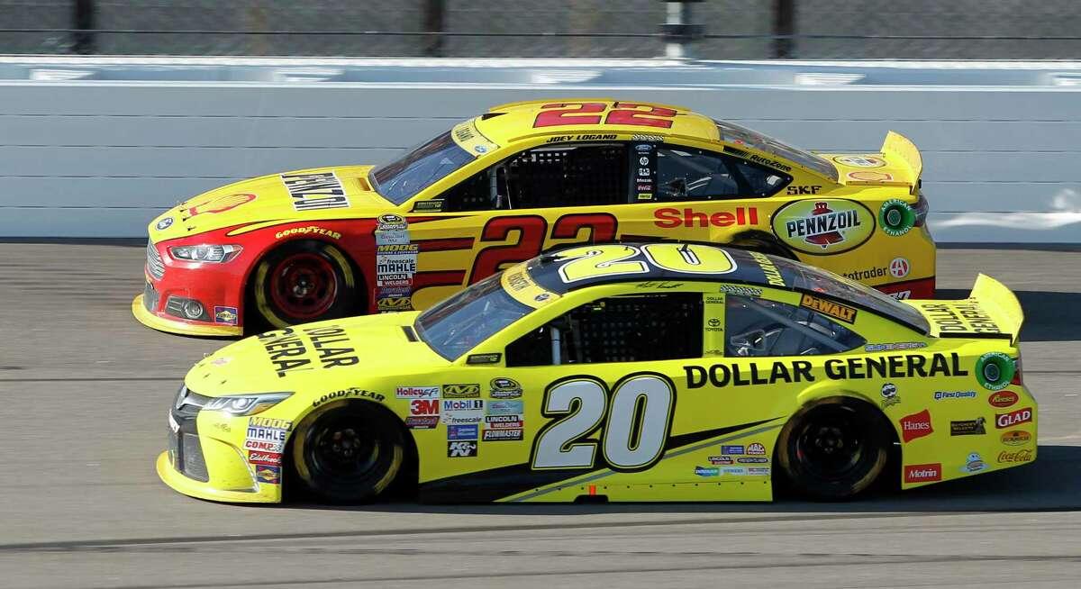 Joey Logano (22) and Matt Kenseth (20) run side-by-side during Sunday's race at Kansas Speedway in Kansas City, Kan.