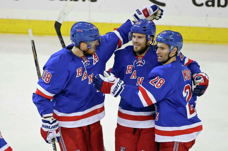 The Rangers' Viktor Stalberg, center, celebrates with Marc Staal, left, and Dominic Moore after a goal in the third period on Monday. The Rangers won 4-0. Photo: Frank Franklin II — The Associated Press  / AP