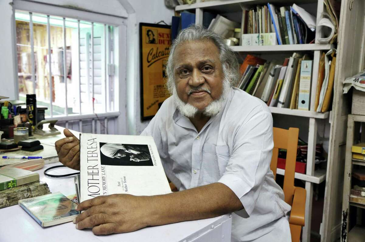 """In this Aug. 29, 2016, photo, freelance photographer Sunil K. Dutt displays his book on Mother Teresa in Kolkata, India. Dutt began covering Mother Teresa's work in Kolkata in 1965 and has one of the largest collections of photographs of the nun. """"From the day I first met her Mother always appeared to me a living saint in action,"""" the 80-year-old said. """"My association with Mother Teresa has impacted my life in a very big way. Whenever I think of her I feel a profound peace in the very core of my heart."""""""