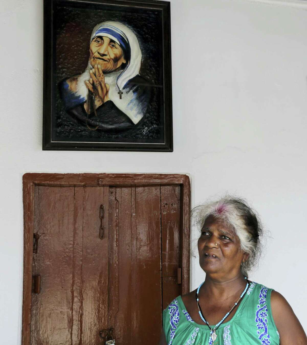 In this Aug. 28, 2016, photo, Bertha Mondal stands beside a portrait of Mother Teresa and speaks with the Associated Press in Kolkata, India. For Mondal, Mother Teresa is more than a saint. The 60-year-old grew up at an orphanage run by the Missionaries of Charity. Now she works as a caretaker at the home.