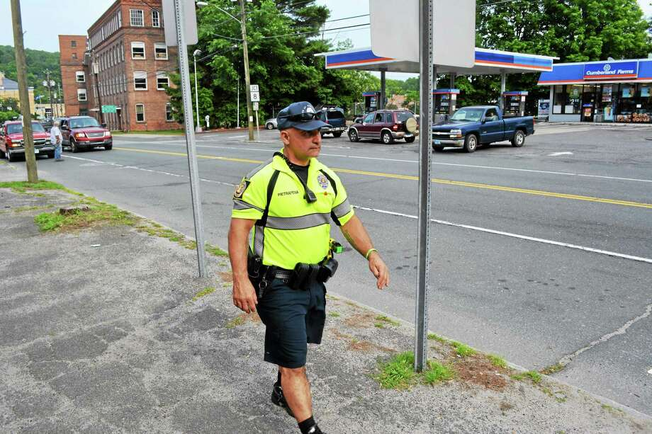 Winchester police officer Daniel Pietrafesa walks through downtown Winsted while conducting a foot patrol. Photo: Journal Register Co.