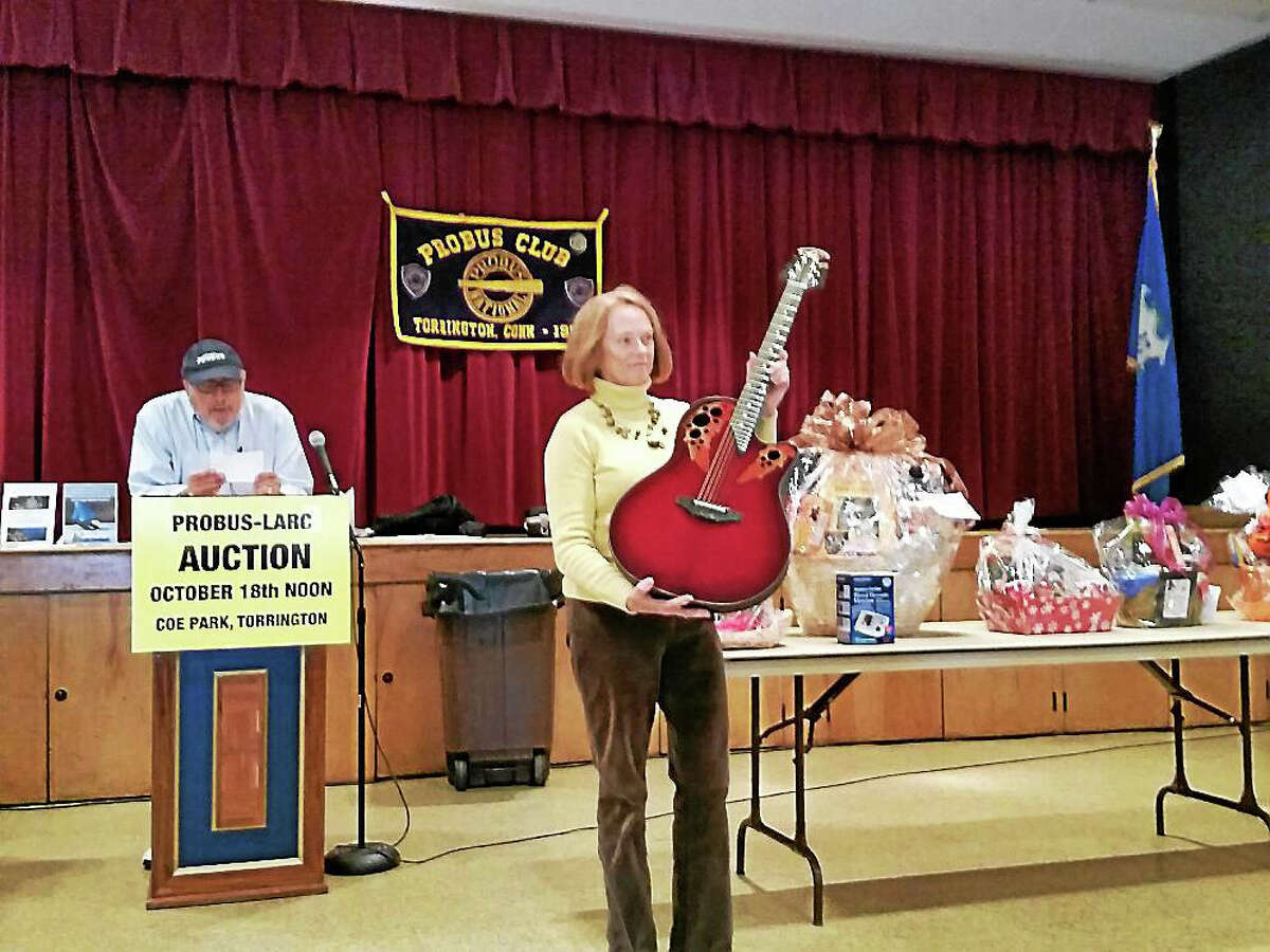 Volunteer and LARC board member Ann Bowen displayed a donated Ovation electric guitar worth $1,569 for auction at the 46th Annual PROBUS Club/LARC Auction.