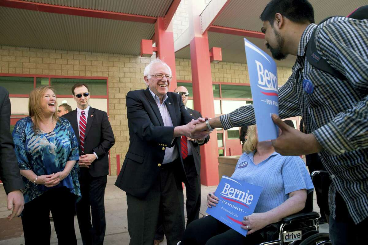 Democratic presidential candidate Sen. Bernie Sanders, I-Vt., center, shakes hands with voters as his wife, Jane, left, watches at a caucus site, Saturday, Feb. 20, 2016, in Las Vegas.
