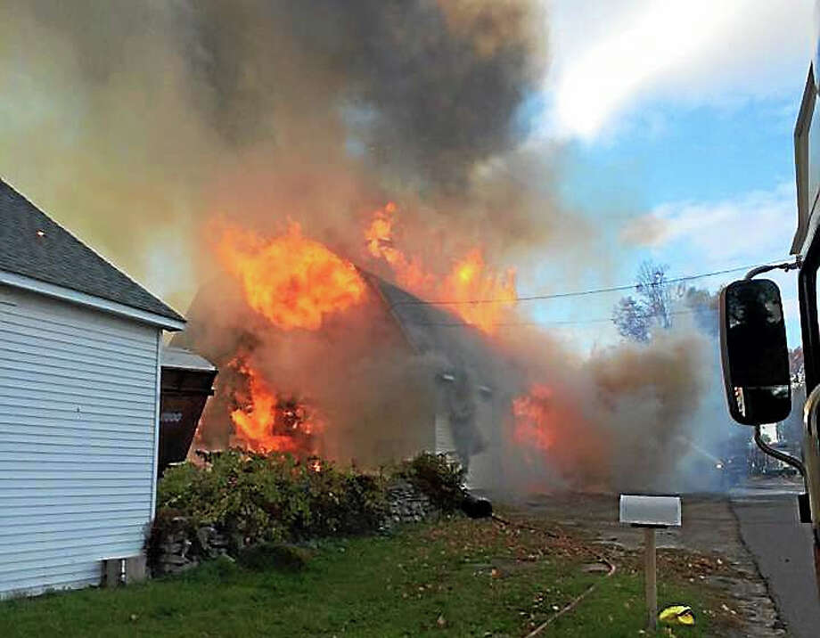 Firefighters from around the region worked for several hours Sunday evening to control a barn fire on Ridge Road. A large amount of hay inside the barn fueled the flames, which shot through the roof. Photo: Photo From Water Witch Hose Co. #2