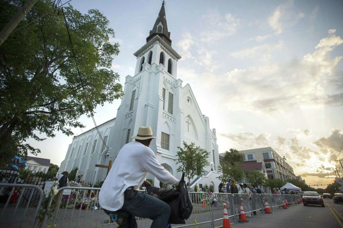 A bicyclist rides in front of the Emanuel AME Church, Sunday, June 21, 2015, before the first worship service since nine people were fatally shot at the church during a Bible study group, in Charleston, S.C.