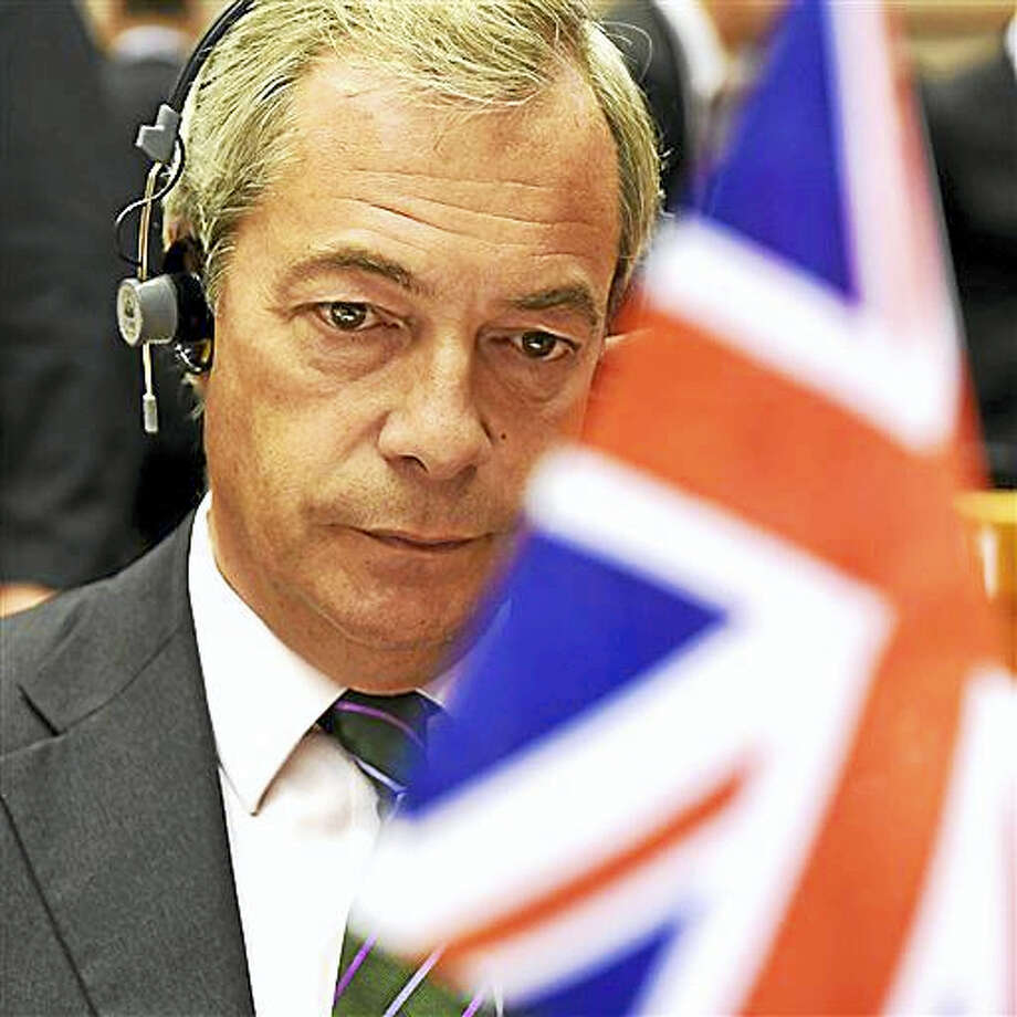 Leader of the UKIP Nigel Farage sits behind a British flag during a special session of European Parliament in Brussels on Tuesday, June 28, 2016. EU heads of state and government meet Tuesday and Wednesday in Brussels for the first time since Britain voted to leave the European Union, throwing British and European politics into disarray. Photo: AP Photo/Geert Vanden Wijngaert   / AP