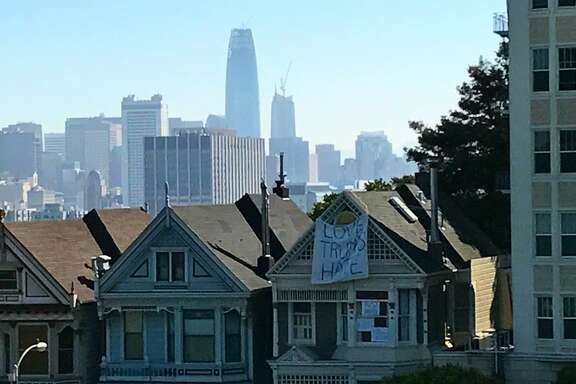 "A banner hangs from one of the ""Painted Ladies"" across from Alamo Square Park in San Francisco."