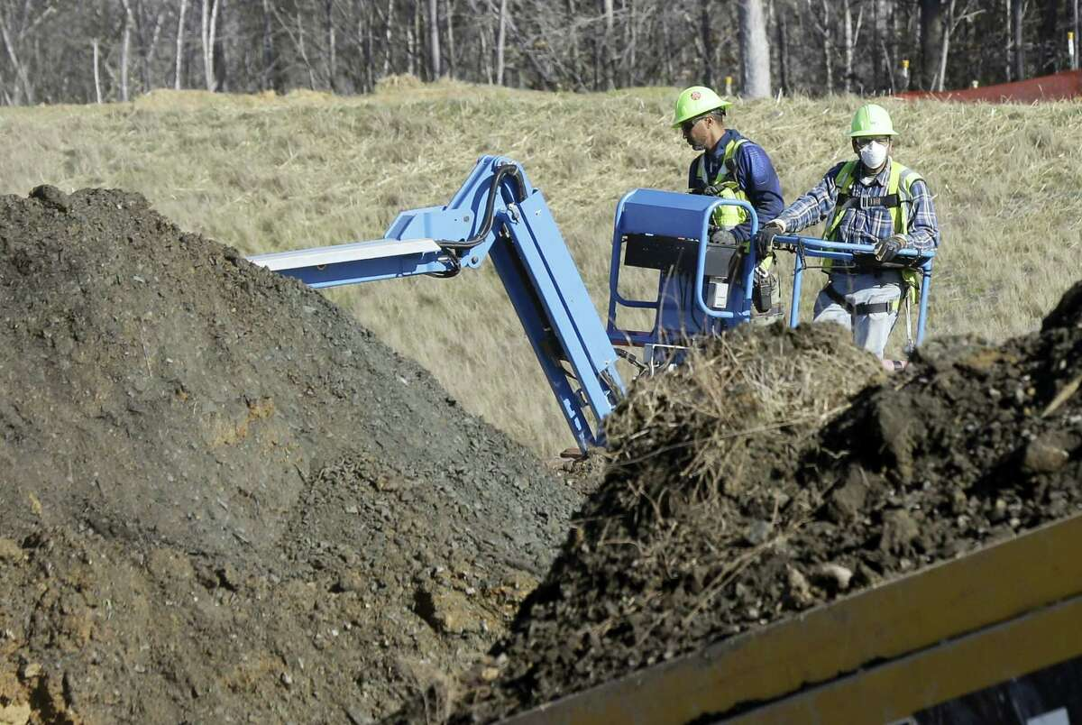 Workers excavate coal ash-laden soil to be removed from the Dan River Steam Station in Eden, N.C.
