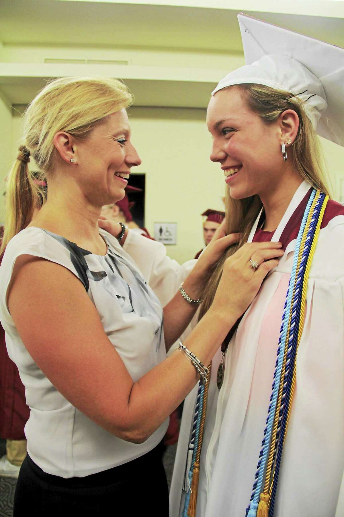 Anita Garnett -- Register-Citizen State Rep. Michelle Cook spends a joyful moment with her daughter before the ceremony.