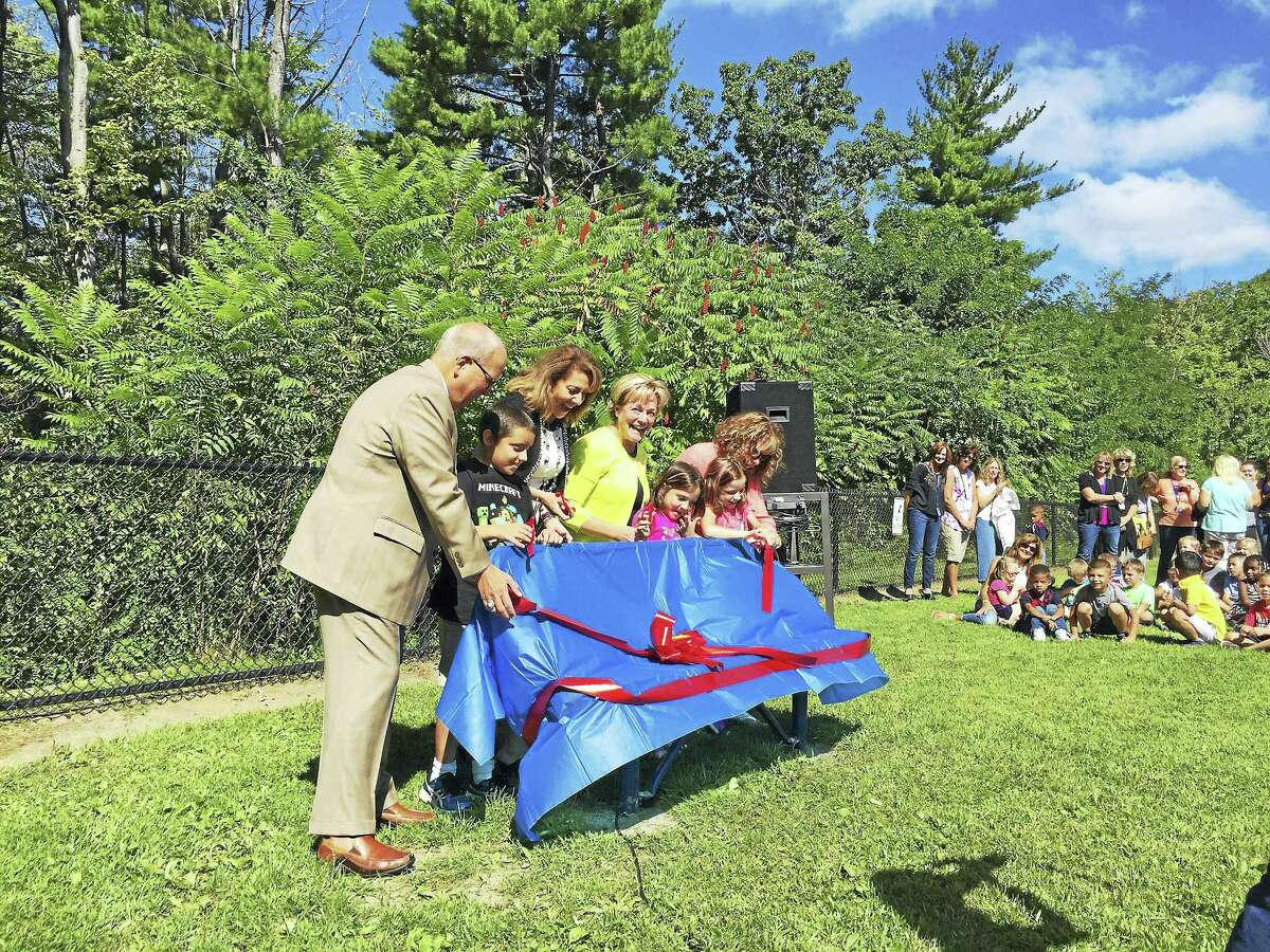 Ben Lambert - The Register Citizen A new Buddy Bench was unveiled Friday morning at Torringford School in Torrington. Above, students, teachers and Mayor Elinor Carbone, in yellow, cut the ribbon on the bench, which is intended to help children find playmates during recess.